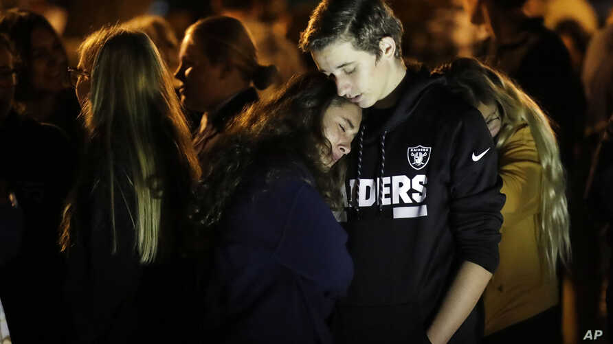 Hannah Schooping-Gutierrez, center, a student at Saugus High School, is comforted by her boyfriend Declan Sheridan, at right, a…