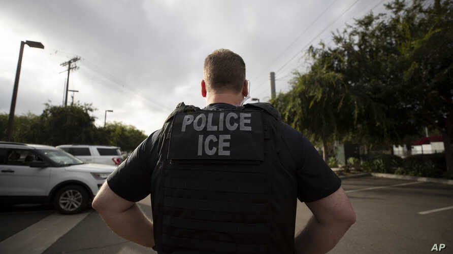 FILE - In this July 8, 2019, file photo, a U.S. Immigration and Customs Enforcement (ICE) officer looks on during an operation…