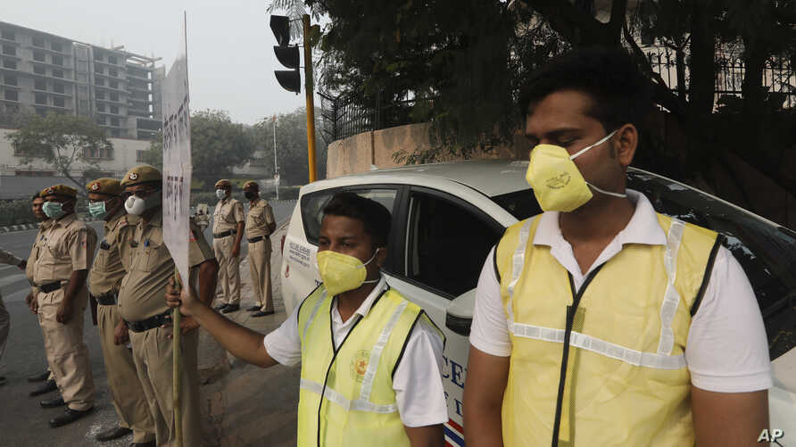 Volunteers and policemen wear pollution masks and stand at a busy crossing with the banner saying obey odd and even, remove…