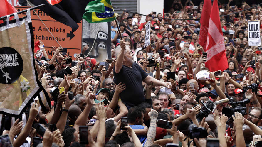 Former Brazilian President Luiz Inacio Lula da Silva is carried by supporters through a jubilant crowd during a rally at the…
