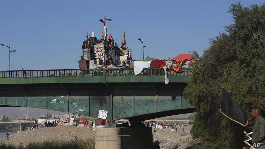 Anti-government protesters stage a sit-in on a bridge leading to the Green Zone government areas, during ongoing protests in…