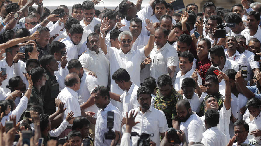 Sri Lanka's newly elected president Gotabaya Rajapaksa, center, greets people as he leaves after the swearing in ceremony held…