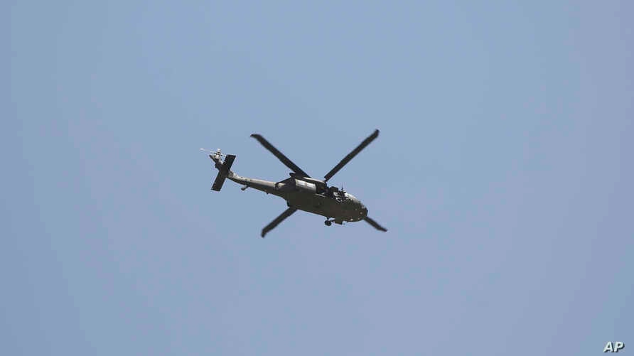A U.S. military helicopter flies over the site of a suicide car bomb in Kabul, Afghanistan, Friday, May 31, 2019. In a second…