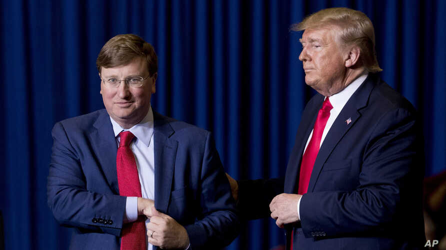 President Donald Trump welcomes Mississippi Lt. Gov. Tate Reeves, left, to the stage at a rally at BancorpSouth Arena in Tupelo…