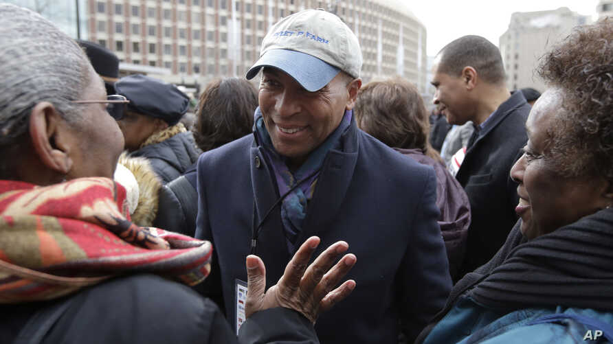 Former Mass. Gov. Deval Patrick, center, greets people in a crowd, Monday, April 2, 2018, before a remembrance on City Hall…
