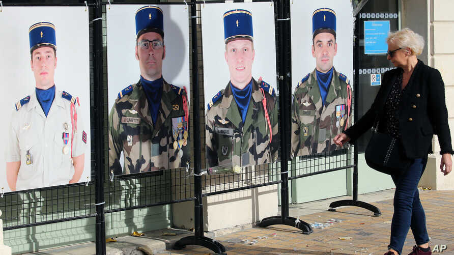 A woman looks at portraits of French soldiers, from left, Clement Frison Roche, Julien Carette, Pierre Bockel and Benjamin…
