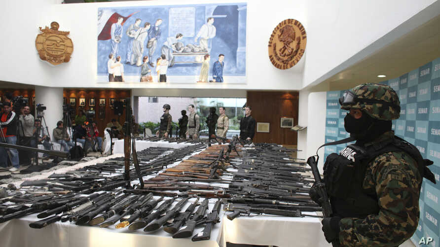 A soldier stands next to seized weapons during a presentation for the press in Mexico City, Thursday, June 9, 2011. Over 200…