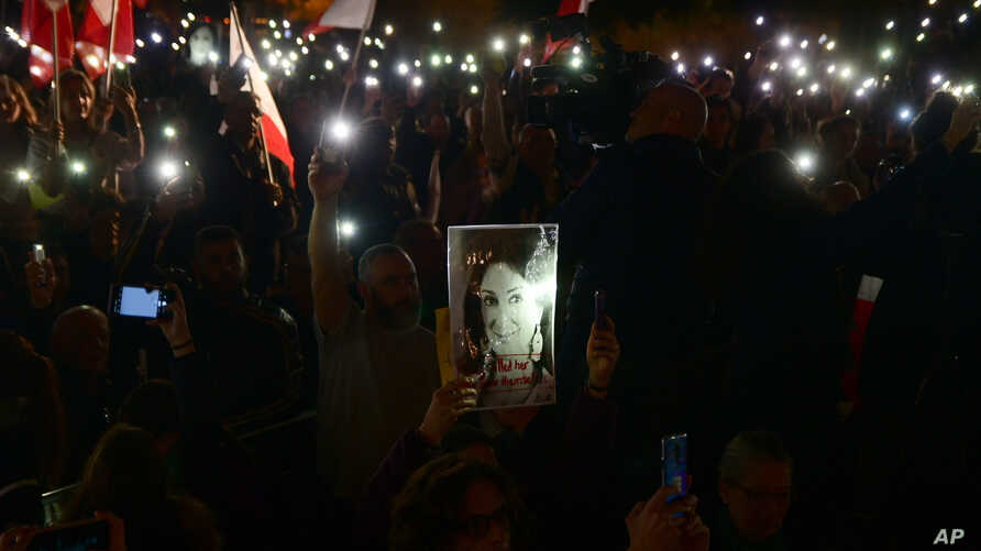 Protestors hold up a pictures of slain journalist Daphne Caruana Galizia during a demonstration outside Malta's prime minister…