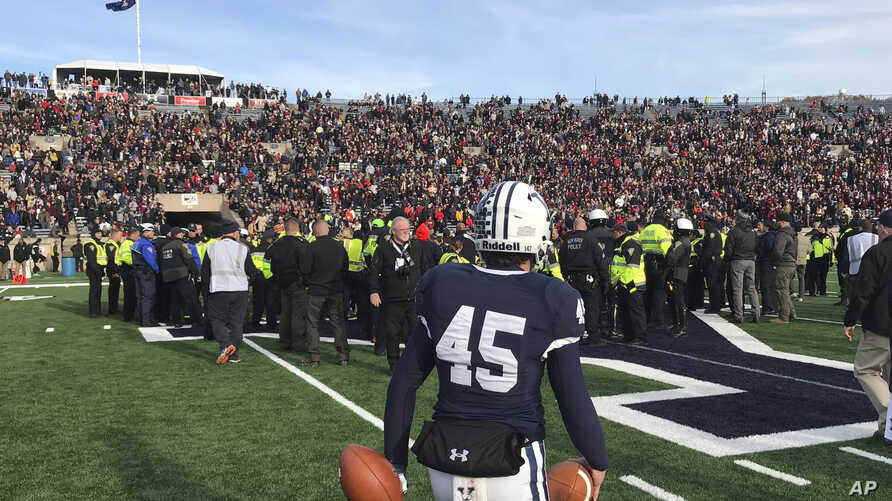 Yale punter Jack Bosman watches as demonstrators stage a protest on the field at the Yale Bowl disrupting the start of the…