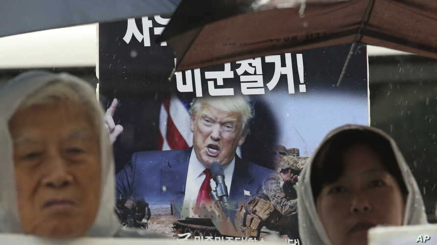 Protesters with an image of U.S. President Donald Trump stage a rally to oppose the United States' policies against North Korea…