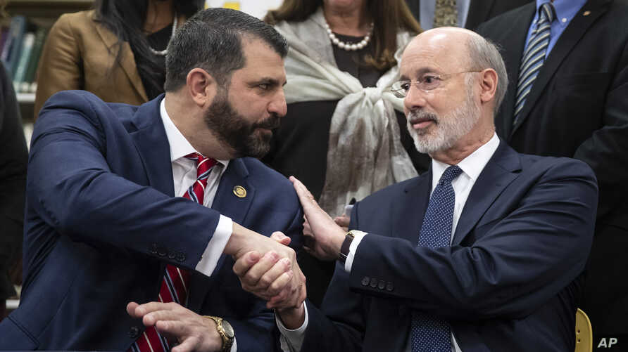 Pennsylvania Gov. Tom Wolf, right, shakes hands with Rep. Mark Rozzi, D-Berks, after signing legislation into law at Muhlenberg…