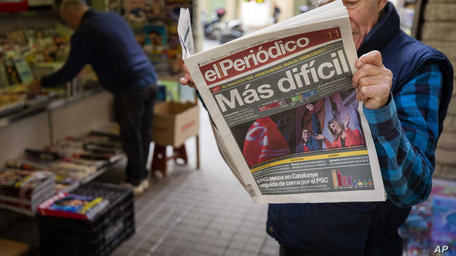 A man reads a newspaper at a newsstand in Barcelona, Spain
