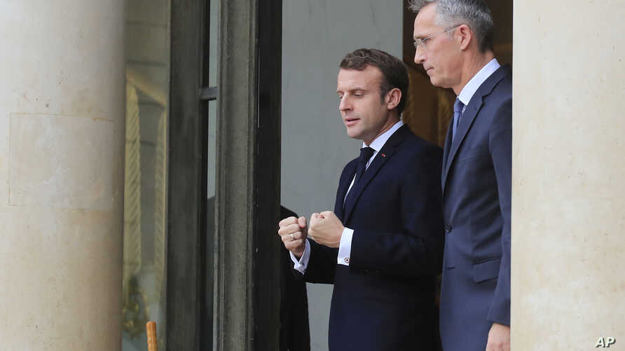 French President Emmanuel Macron, left, and NATO Secretary General Jens Stoltenberg walk out of the lobby after a meeting at…