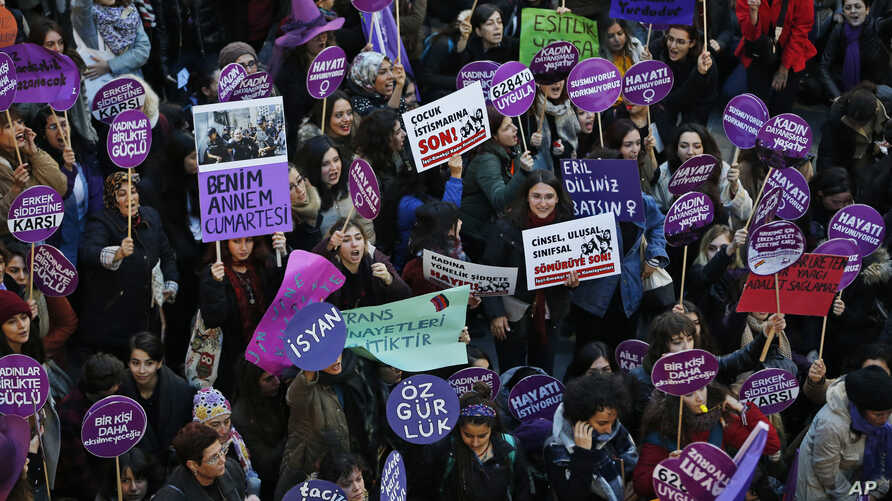 Protesters, mostly women, display various placards calling to end violence towards women, and chant slogans during a rally in…