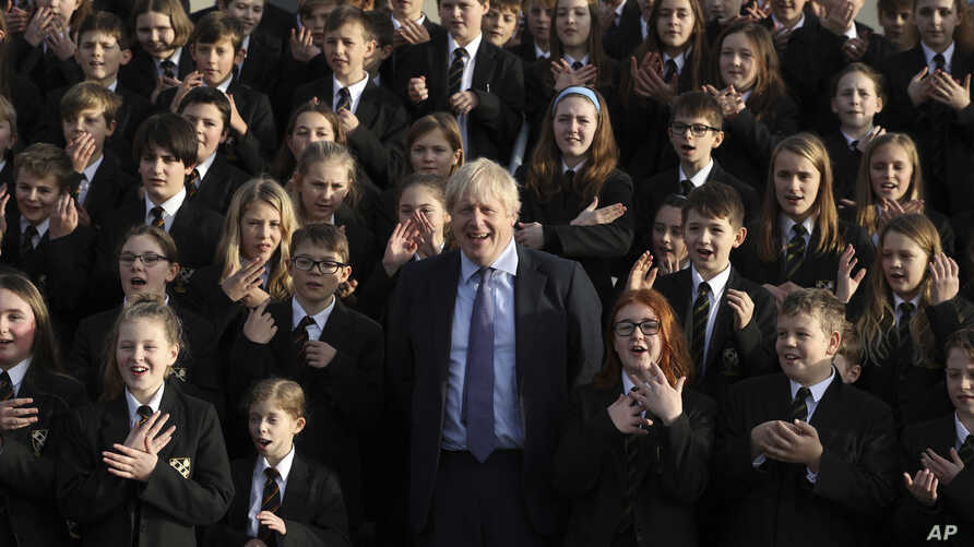 The Chulmleigh College school choir sings and signs 'A Lovely Day' as Britain's Prime Minister and Conservative Party leader,…