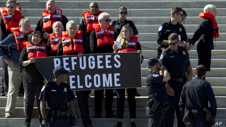 Faith leaders and members of human rights groups wearing a life vests symbolizing the life-saving program are arrested by U.S…