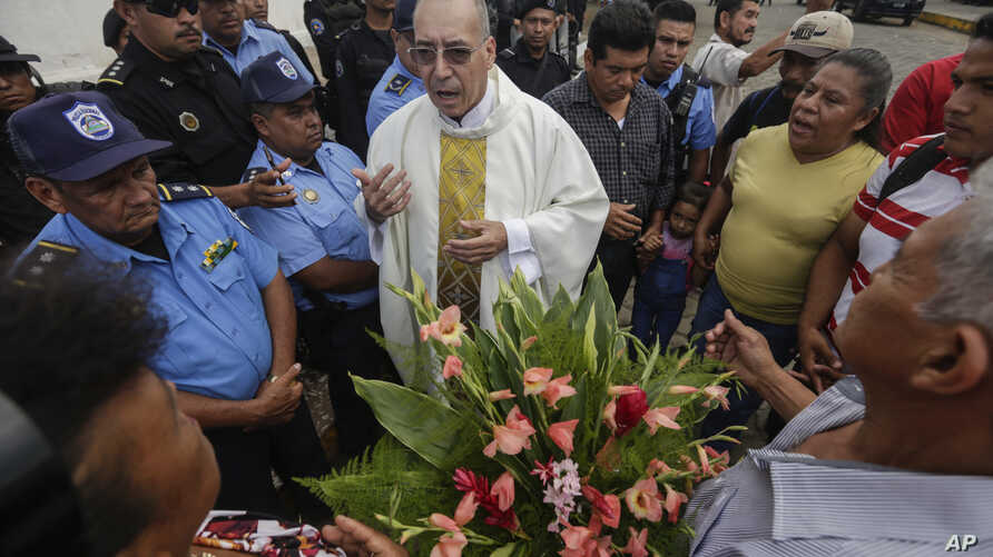 Father Edwin Roman attempts to convince the police to allow relatives of imprisoned and dead anti-government demonstrators to…