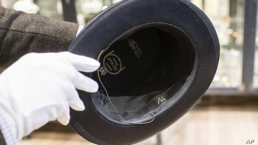 A man holds a hat with the initials of Adolf Hitler prior to an auction in Grasbrunn, Germany, Wednesday, Nov. 201, 2019. A…
