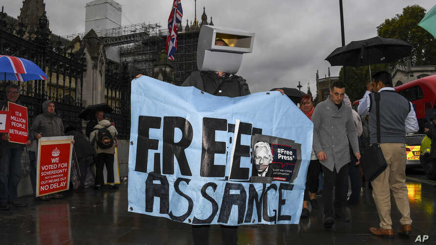 A supporter of Julian Assange protests outside the Houses of Parliament, in London, Monday, Oct. 21, 2019.  Assange is detained…