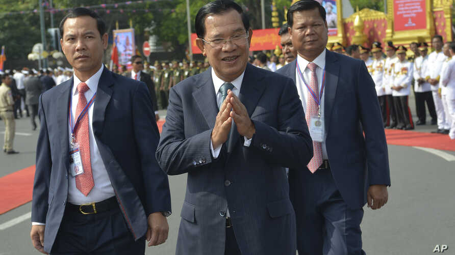 Cambodian Prime Minister Hun Sen, center, greets his government officers during the country's 66th Independence Day from France…