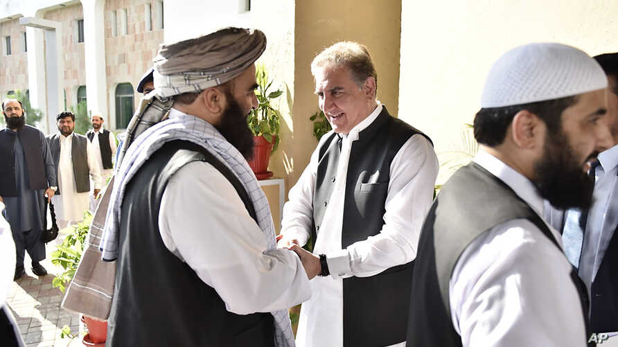 In this photo released by the Foreign Office, Pakistan's Foreign Minister Shah Mehmood Qureshi, center, receives members of…
