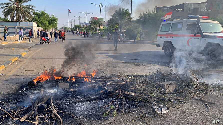 Protesters set fire to close a street in Sadr City, baghdad