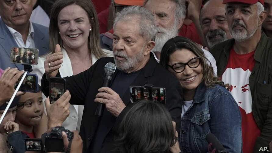 Brazil's former President Luiz Inacio Lula da Silva speaks to supporters as his girlfriend Rosangela da Silva leans on his back…