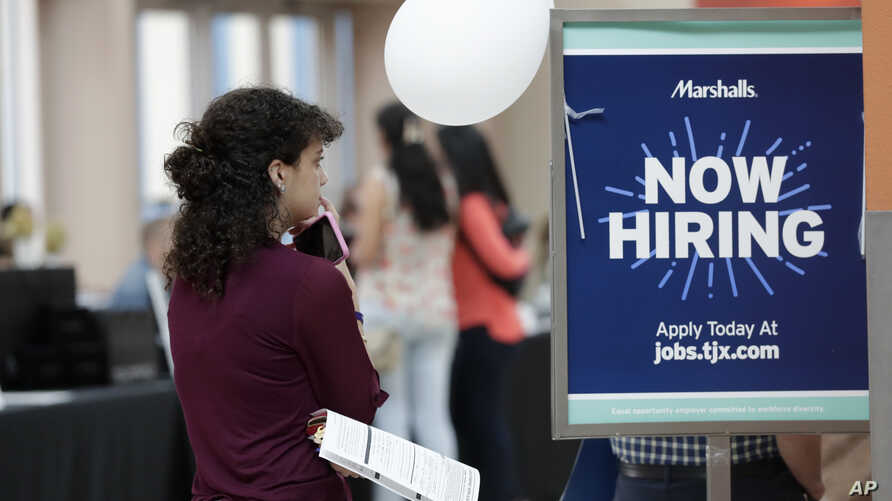 FILE - In this Oct. 1, 2019, file photo, Daisy Ronco waits in line to apply for a job with Marshalls during a job fair at…