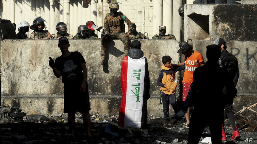 Iraqi security forces and anti-government protesters rest after both sides shake hands and converse in a rare moment of calm in…