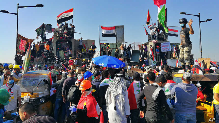 Anti-government protesters control some barriers set by Iraqi security forces to close the bridge leading to the Green Zone…