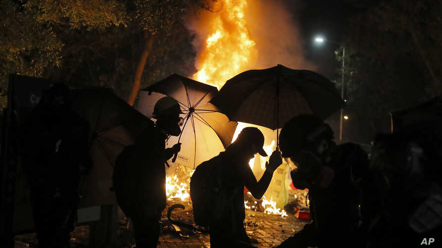 Students walk by a fire during a clash with police at the Chinese University in Hong Kong, Tuesday, Nov. 12, 2019. Police and…