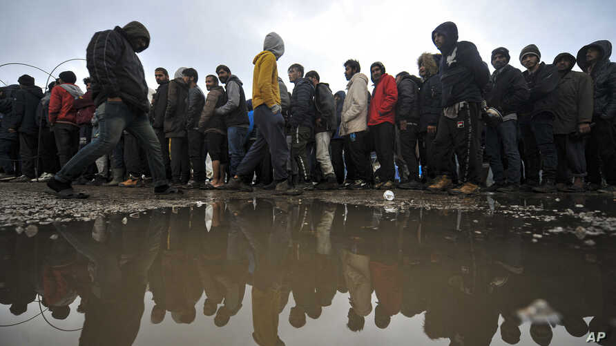 In this Wednesday, Nov. 20, 2019, photograph migrants wait in line for a warm meal at the Vucjak refugee camp outside Bihac,…