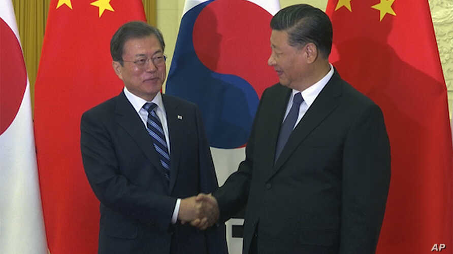 In this image from video, South Korean President Moon Jae-in, left, is great by his Chinese counterpart Xi Jinping ahead of…