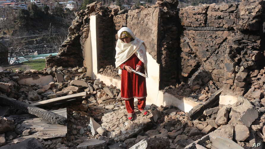 A Pakistani Kashmiri woman stands amid debris of her home that reportedly was destroyed by cross border shelling from Indian…