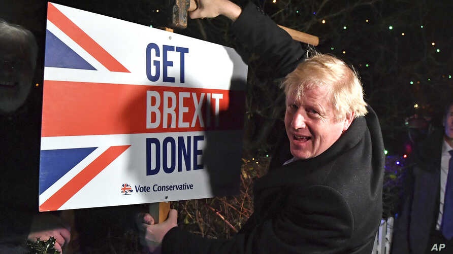 "Britain's Prime Minister and Conservative party leader Boris Johnson poses as he hammers a ""Get Brexit Done"" sign into the…"