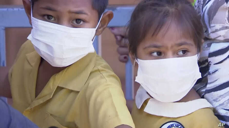 In this November 2019, image from video, masked children wait to get vaccinated at a health clinic in Apia, Samoa. Samoa closed…