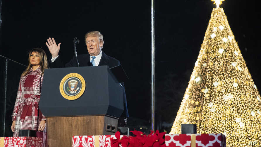 President Donald Trump with first lady Melania Trump waves during the National Christmas Tree lighting ceremony at the Ellipse…