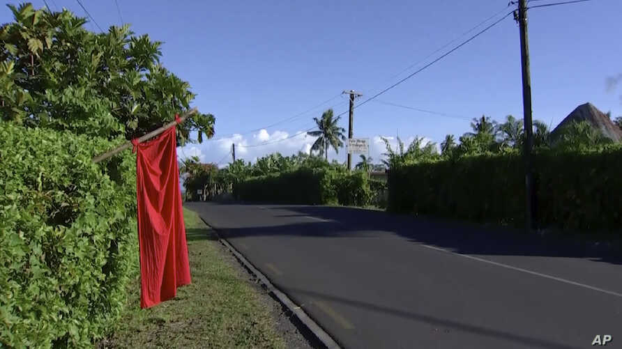 In this image from video, a red flags hangs outside homes of residents who have not been vaccinated in Apia, Samoa, Thursday,…