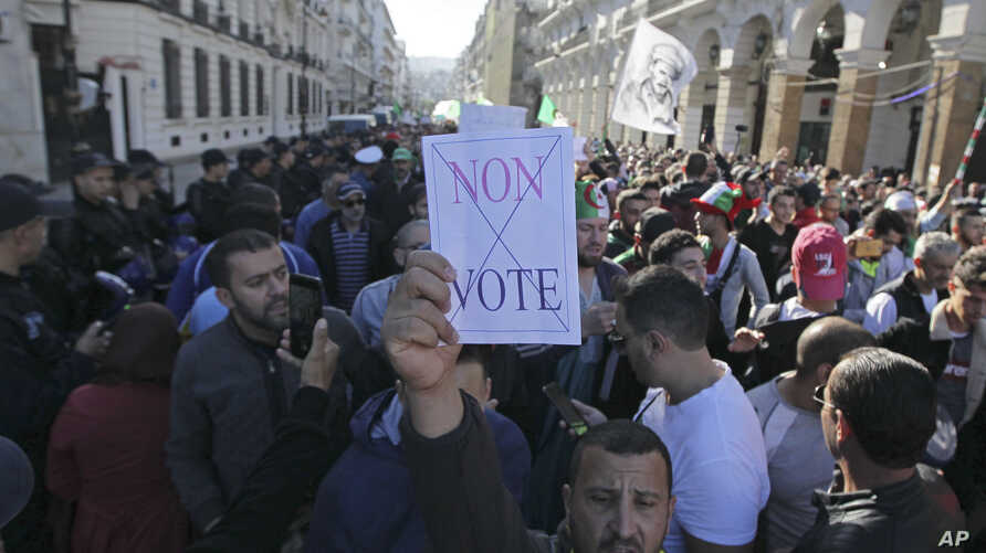 "An Algerian demonstrator holds a placard that reads ""no vote"" during a protest against the government and the upcoming…"