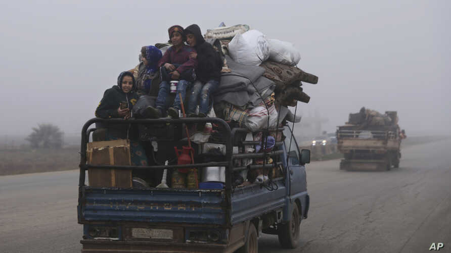 Civilians ride in a truck as they flee Maaret al-Numan, Syria, ahead of a government offensive, Monday, Dec. 23, 2019. (AP…