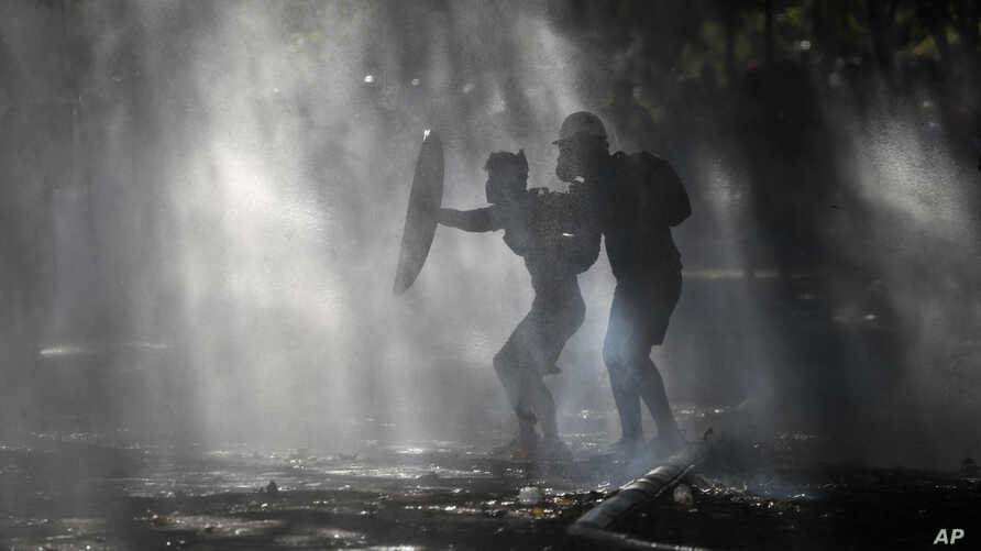 Anti-government demonstrators shield themselves amid the spray of a police water cannon trying to disperse them in Santiago,…