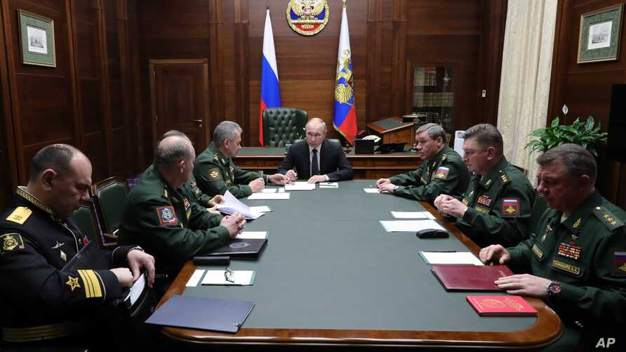 Russian President Vladimir Putin, center, leads a meeting with top military officers after an annual meeting with top military…