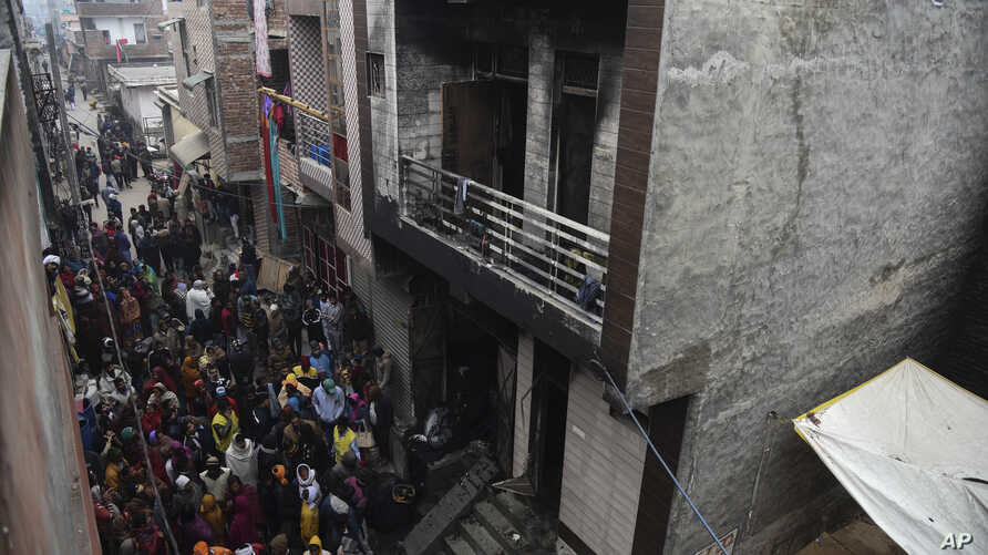 People gather around a warehouse where a fire broke out in the early hours of Monday at Kirari area of New Delhi, India, Monday…
