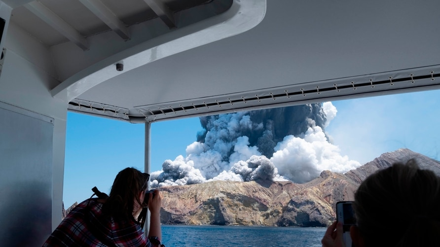 FILE - In this Dec. 9, 2019, file photo provided by Michael Schade, tourists on a boat look at the eruption of the volcano on…
