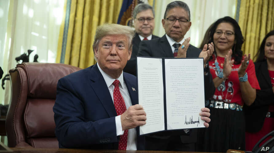 President Donald Trump shows an executive order establishing the Task Force on Missing and Murdered American Indians and Alaska…
