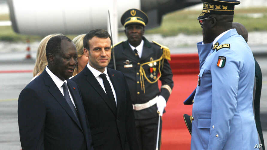 French President Emmanuel Macron is welcomed by President Alassane Ouattara upon arrival in Abidjan, Ivory Coast, Friday Dec…