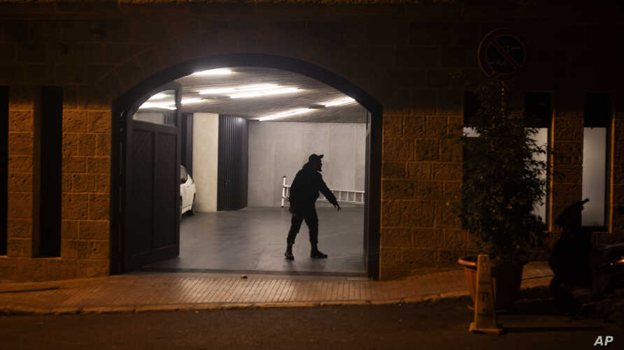 A security guard stands in the garage at the residence of former Nissan Chairman Carlos Ghosn on Monday, Dec. 30, 2019 in…