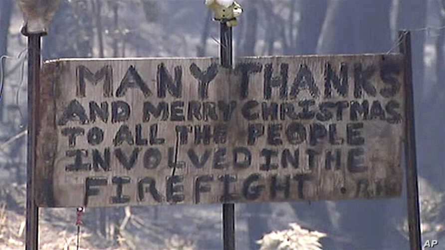 In this image made from video, a sign offers thanks and a Merry Christmas in a destroyed residential area by wildfire, Monday,…