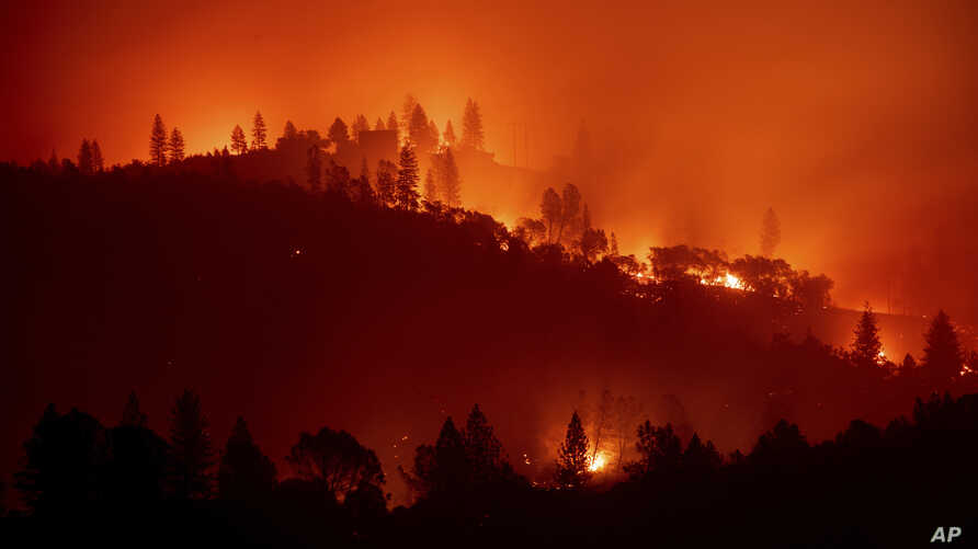 FILE - In this Nov. 10, 2018, file photo, the Camp Fire burns along a ridgetop near Big Bend, Calif. Pacific Gas and Electric…