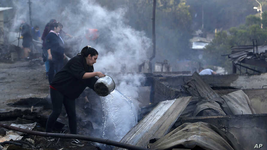 Residents spray water over remains of their homes after a wildfire damaged dozens of houses on the outskirts of Valparaiso,…